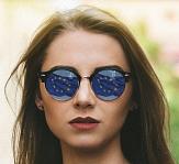 Foto von einer jungen Frau mit Sonnenbrille, in der sich die EU-Flagge spiegelt©Pixabay