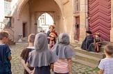 Foto von einer Gästeführerin mit Handpuppe und Kindern in Kostümen, die zuhören©Henrik Isenberg