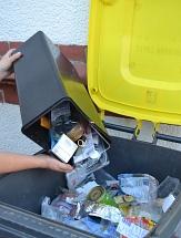 Aus einem kleinen Behälter wird Plastik- und Dosenmüll in die Gelbe Tonne gekippt.©Universitätsstadt Marburg