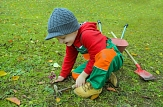Kind, das auf einer Wiese mit Gartenwerkzeugen und Schubkarre spielt©Pixabay