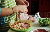 Foto von einer runden Pizza, die gerade belegt wird. Die Zutaten stehen in Glasschüsseln daneben.©Universitätsstadt Marburg
