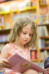 Ein kleines Mädchen betrachtet fasziniert ein aufgeschlagenes Bilderbuch.©Shutterstock_170